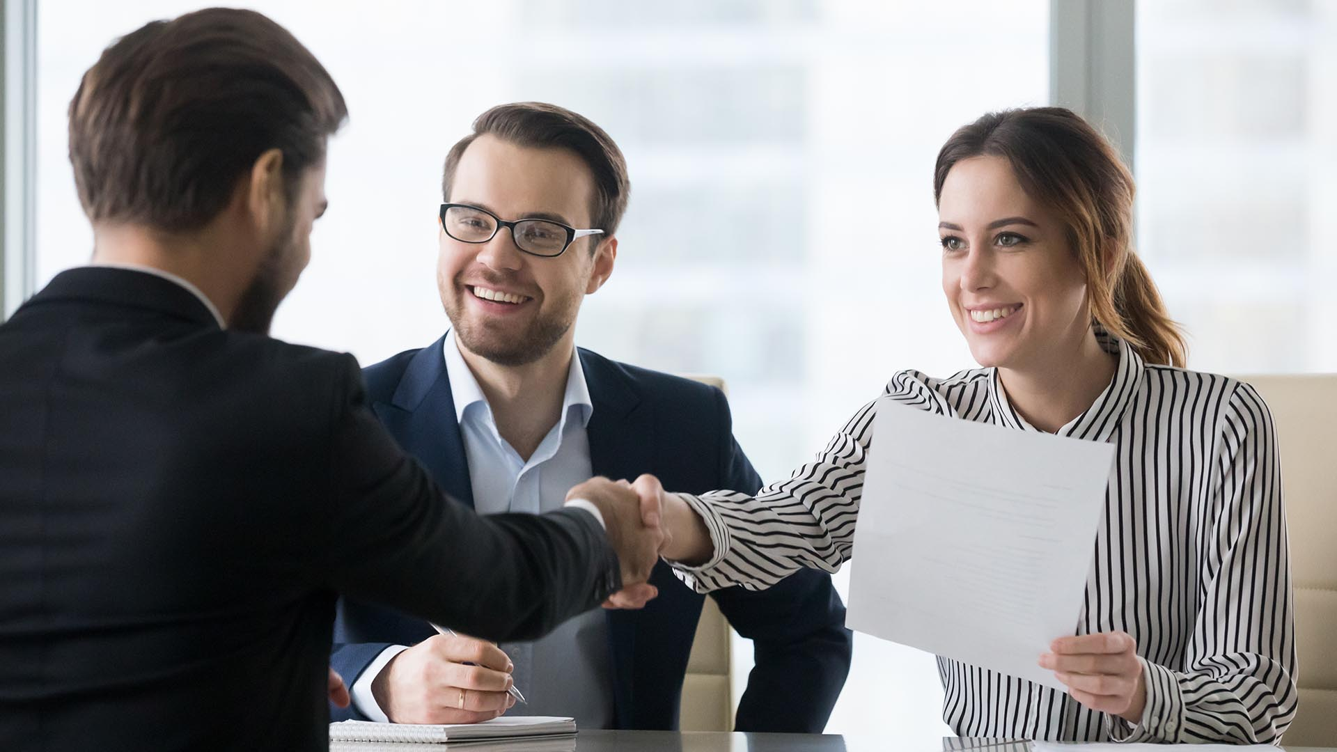 Photo of two business men shaking hands, with Businessness woman next to them