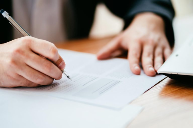Businessman filling official document, signing contract. Business life,agreement, deal done.