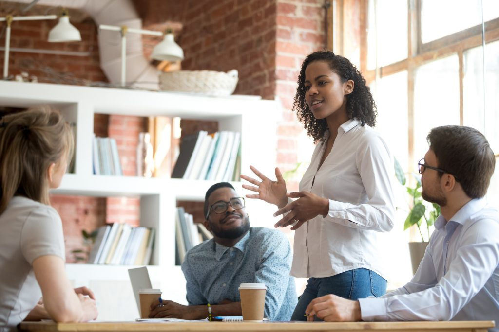 Ambitious smart african black female employee speaking at diverse meeting share creative idea opinion at group briefing while jealous envious skeptical male coworkers looking listening to colleague.